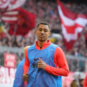 Felix Uduokhai (FC Augsburg #19) im Warmlauftrikot vor der Bayern-Kurve;FC Bayern München vs. FC Augsburg, 25. Spieltag;DFL REGULATIONS PROHIBIT ANY USE OF PHOTOGRAPHS AS IMAGE SEQUENCES AND/OR QUASI-VIDEO.